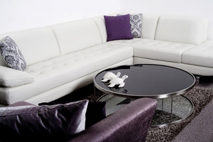 Modern interior of a room with white leather couch and glass table